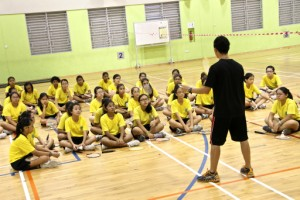 Teacher demonstrating how to play badminton